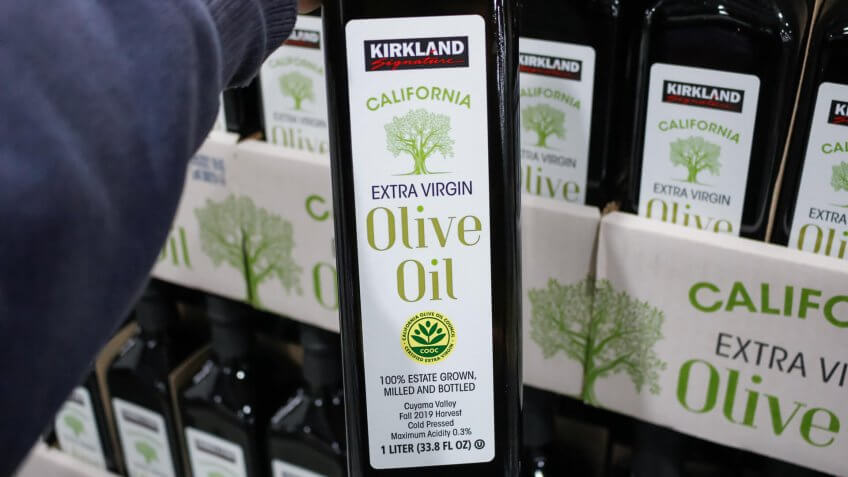 Alhambra, California/United States - 02/19/2020: A hand holds a bottle of Kirkland Signature California Extra Virgin Olive Oil, on display at a local Costco.