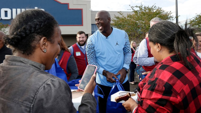 Charlotte Hornets owner Michael Jordan greets people and hands out food for Thanksgiving to members of the community in Wilmington, N.