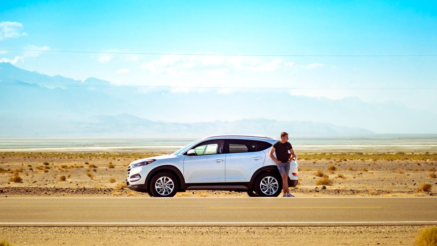 Man standing next to car in desert highway