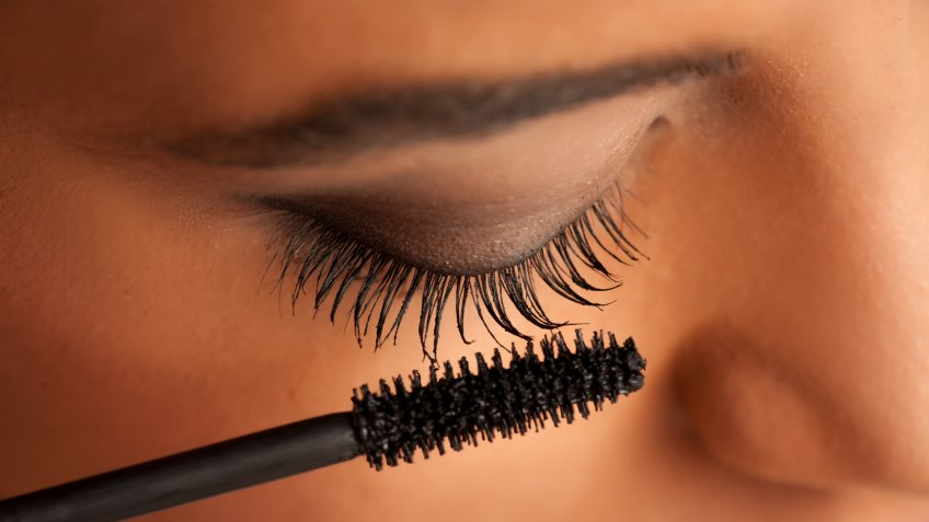 closeup of a young dark-skinned woman applying mascara on a white background.