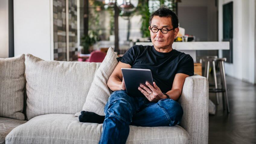 Chinese man in his 50s relaxing at home on sofa, casual clothes, reading ebook, surfing the internet.