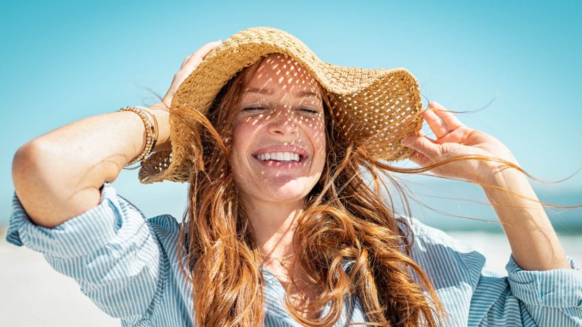 Closeup face of mature woman wearing straw hat enjoying the sun at beach.