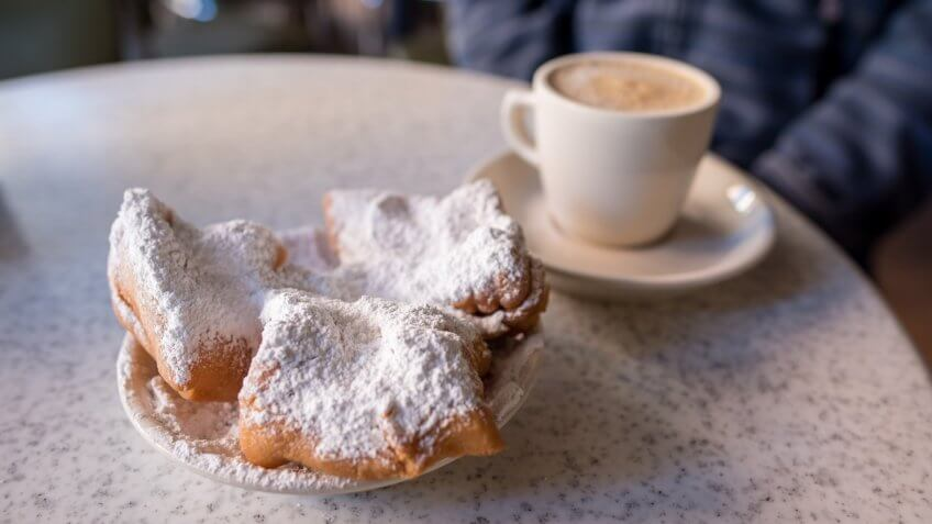 New Orleans, LA, January 25, 2018: Beignets covered with powdered sugar, served with cafe au lait at the famous Cafe Du Monde in the French Quarter.