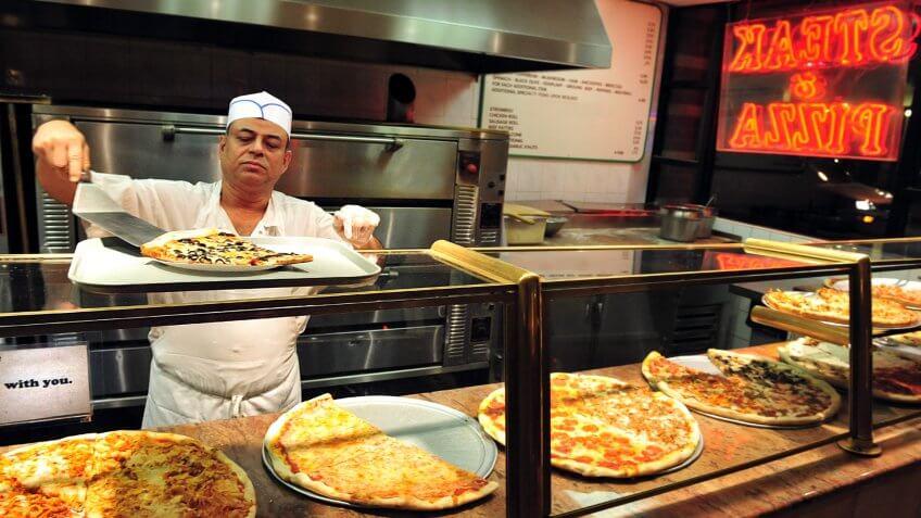 NEW YORK CITY - OCT 11 2009:Pizza chef preparing NYC Pizza Pizzeria restaurant in Manhattan New York.