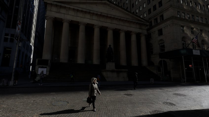 A person walks along a nearly empty Wall Street near the New York Stock Exchange in New York, New York, USA, on 18 March 2020.