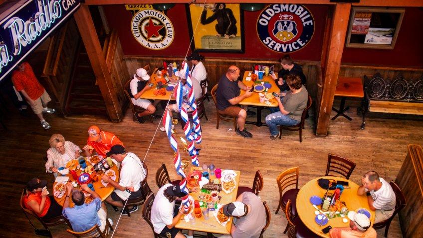 Looking down at people eating, drinking and checking phones at Eskimo Joes bar and resturant near OSU Stillwater Oklahoma USA 05 02 2018.