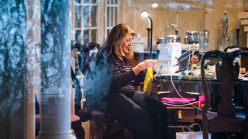 Pat Roth, pictured through her living room window, sews homemade face masks which she donates to George Washington University Hospital in Washington, DC, USA, 28 March 2020.
