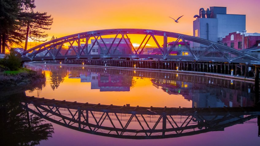 The hues of the rising sun are reflected in the mirror-like surface of the Petaluma River turning basin along the historic Petaluma, California, downtown waterfront.