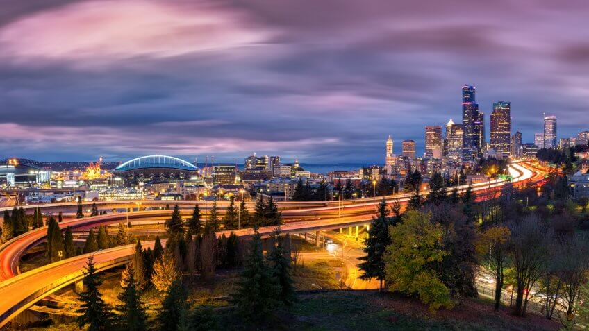Seattle cityscape at dusk with skyscrapers, winding highways parks and sports arenas under a dramatic sky.