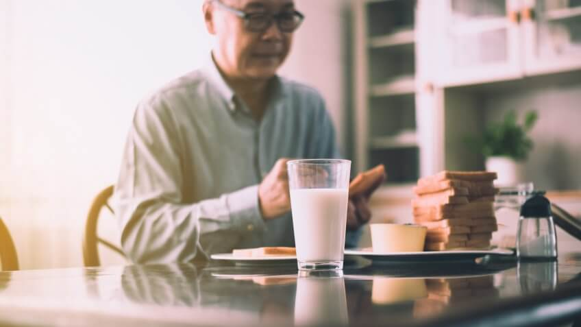 Blurred of asian elderly couple preparing healthy food for breakfast with bread and butter,Retirement senior lifestyle living concept.