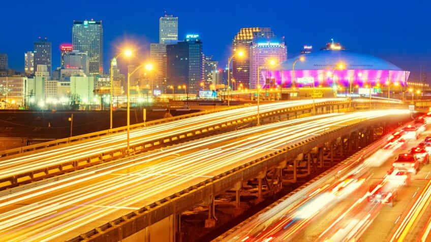 City skyline photo of New Orleans Louisiana USA with traffic on highways, downtown skyscrapers and the Superdome, shot at twilight blue hour.