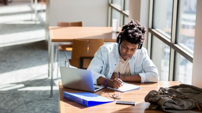 African American teenage boy writes something in a notebook while studying in the campus library.