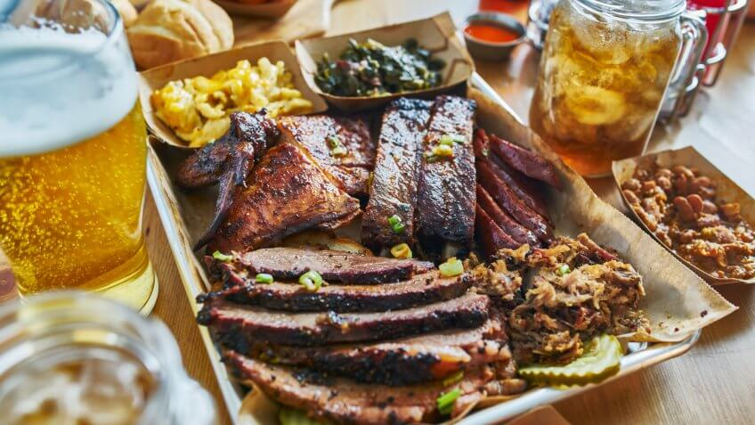 texas style bbq tray with smoked brisket, st louis ribs, pulled pork, chicken, hot links, and sides.