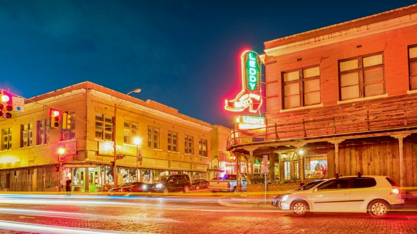 Cars wait at stoplight next to Leddy's Boot store at the landmark Fort Worth Stockyards in Fort Worth, Texas, USA.