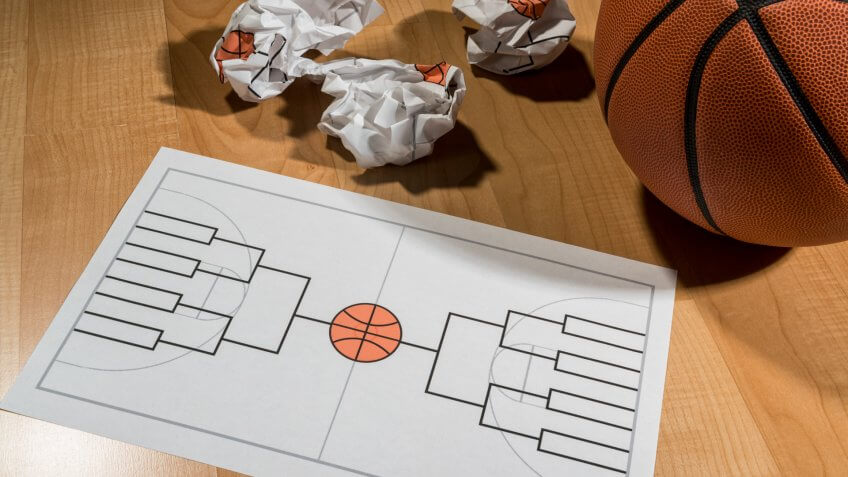 Attempting to fill out a college basketball tournament bracket on a legal size piece of paper with several crumpled balls of paper with failed attempts, sitting on a basketball court with a basketball sitting next to it.