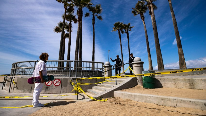 LAPD officers ask a skater to leave the closed skatepark next to the beach amid the coronavirus pandemic in Venice, California, USA, 28 March 2020.