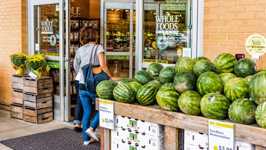 Fairfax, USA - September 8, 2017: female entering Whole Foods Market grocery store building in city in Virginia with autumn displays and watermelons.