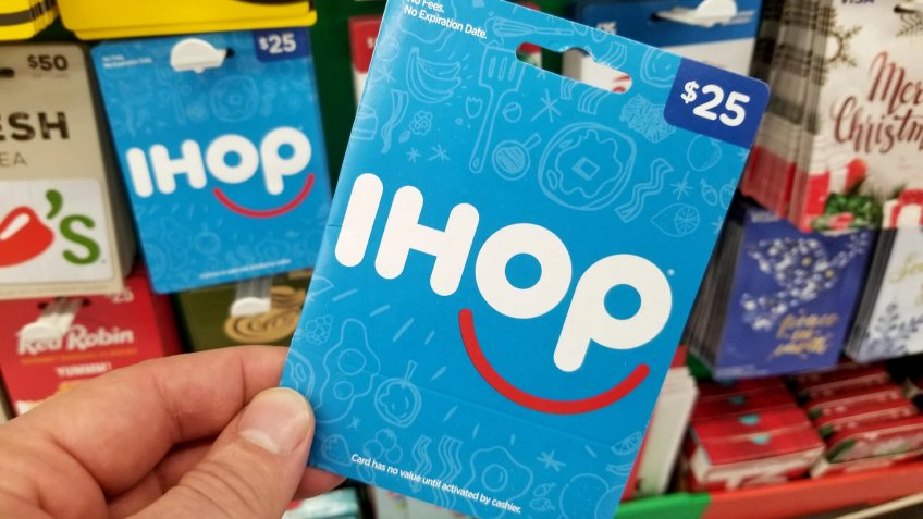 PLATTSBURGH, USA - JANUARY 21, 2019 : IHOP pancake house gift card in a hand over a shelves with different giftcards in a Walmart store.