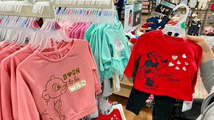 San Jose, CA - November 23, 2019: Young woman looking through clothes on a rack at Walmart store.