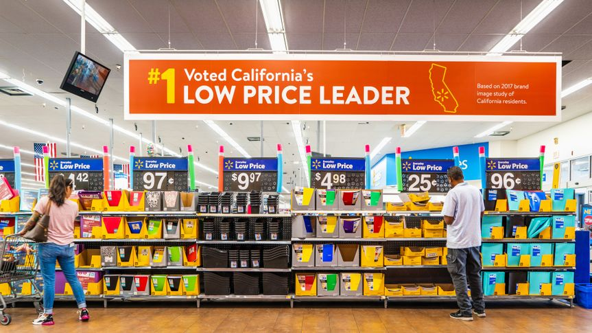 August 8, 2019 Mountain View / CA / USA - People shopping for back to school items in one of the Walmart stores; Banner advertising the low price leader status in California displayed above.