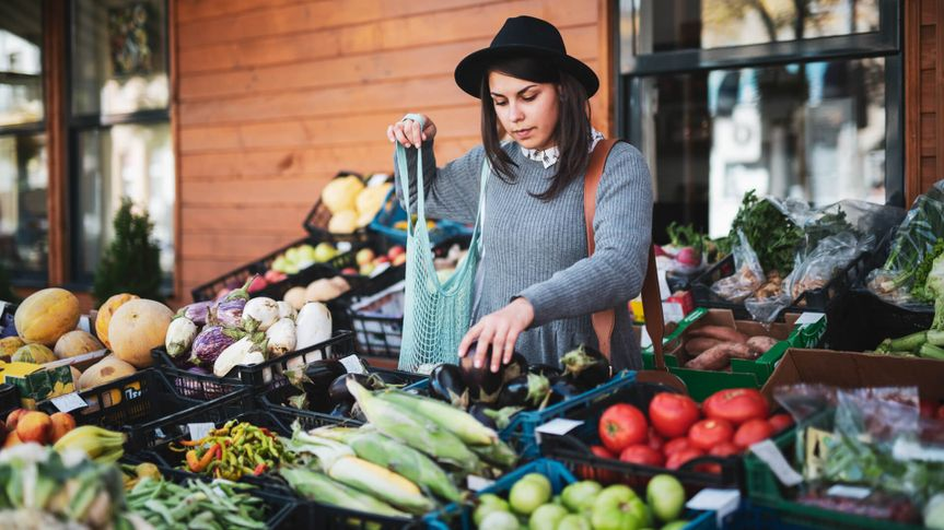 Young woman buying fruit and vegetables at outside market, she choosing eggplant.