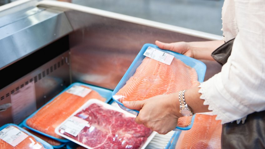 Housewife buying a tray of fresh salmon.