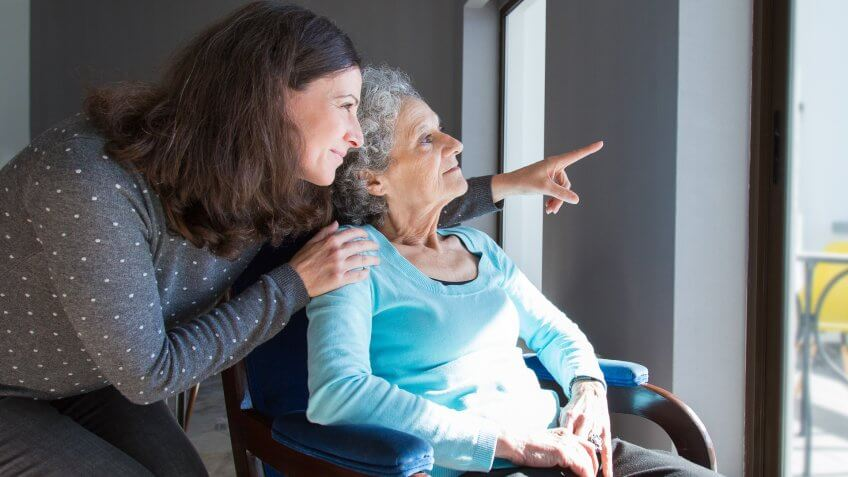 Adult daughter showing to senior mother scene out of window.