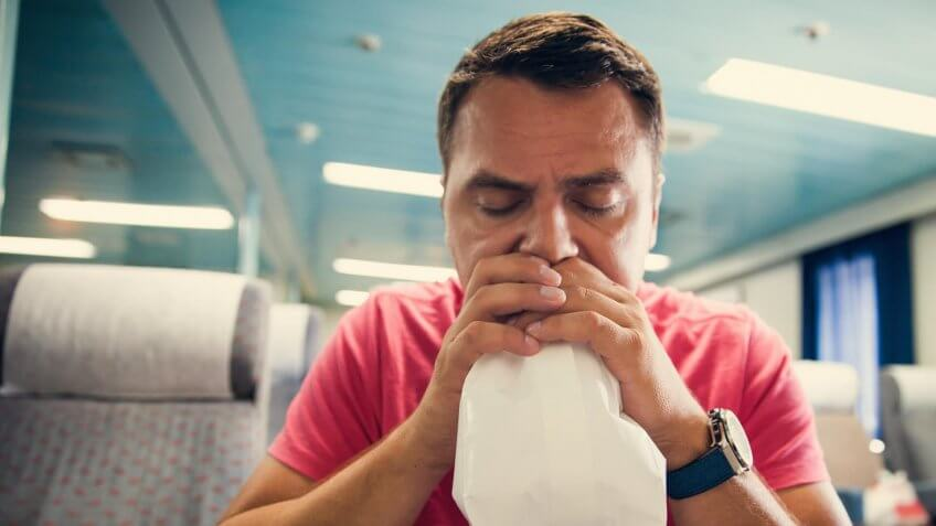 Nauseous man holding a bag to his mouth, hyperventilating.