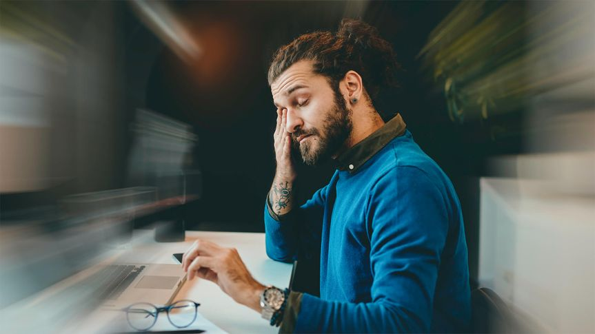 Tired bearded hipster sitting in his office and rubbing his eyes.