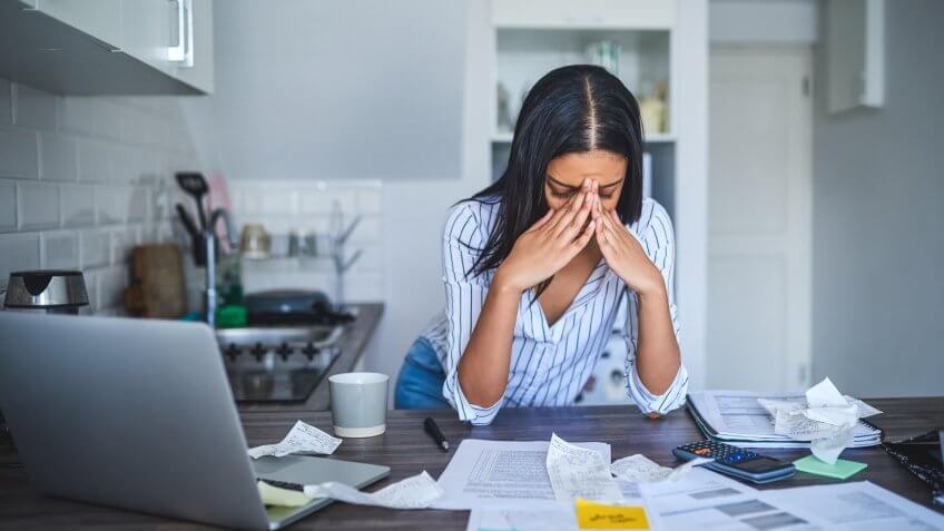 Cropped shot of an attractive young businesswoman standing alone and feeling stressed while going through her finances in her home.