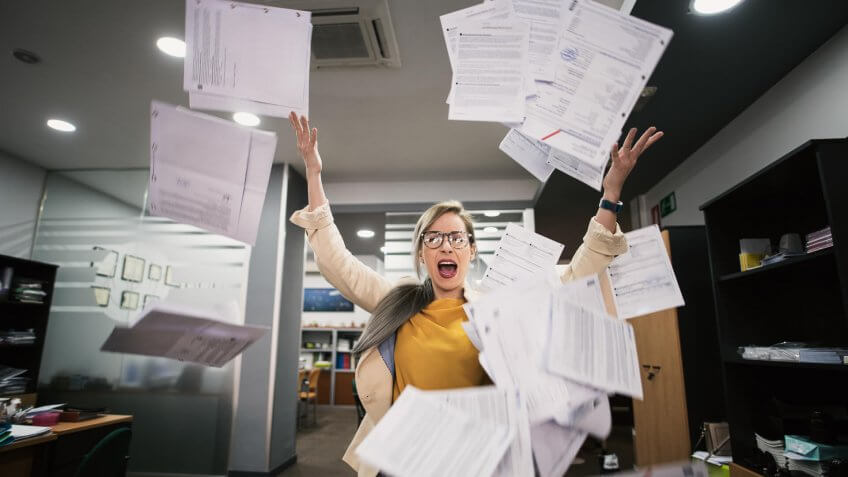 Stressed woman throws papers in the office in an image of relief.