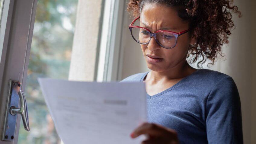 Sad black woman near window reading bad news letter.