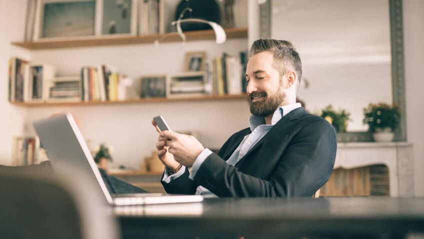 bearded man using smartphone in homeoffice.