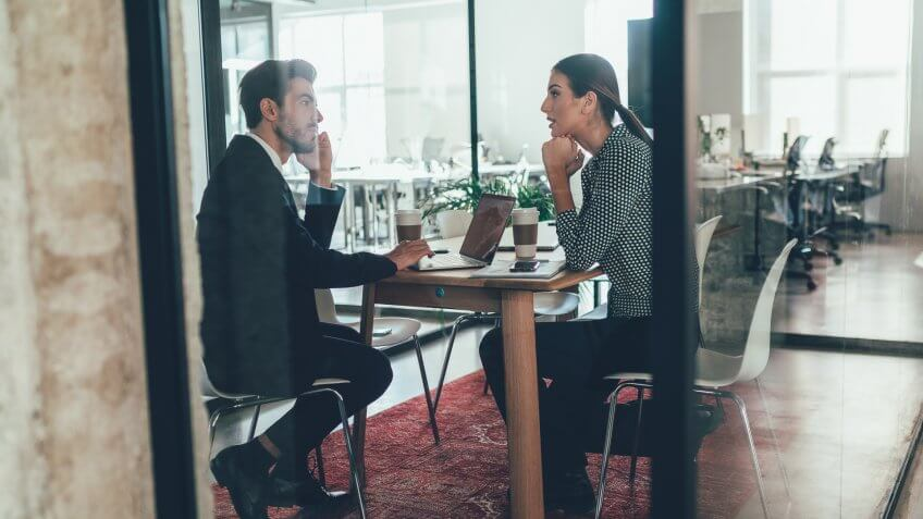 Businessman and business woman talking in the office.