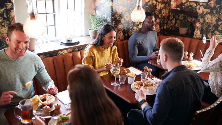 Group Of People Eating In Restaurant Of Busy Traditional English Pub.