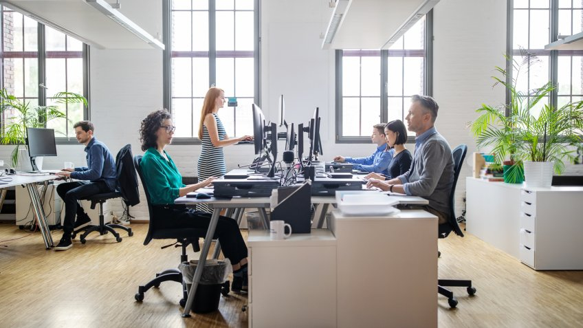 Business people at their desks in a busy, open plan office.