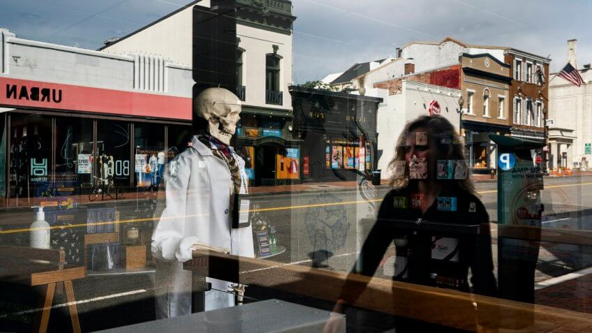 A woman is reflected in a shop window with a skeleton on display at a normally busy M Street in Georgetown is near empty before lunch hour in Washington, DC, USA, 27 March 2020.