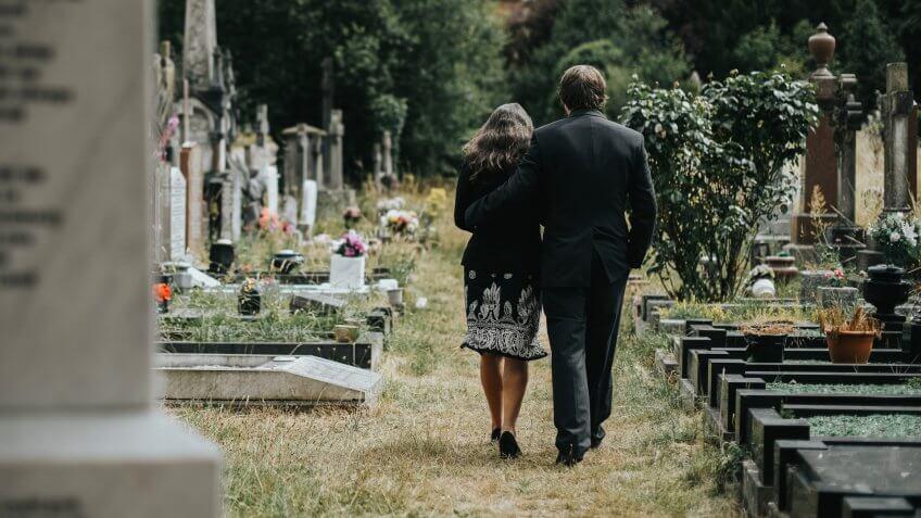 Sad couple walking through a cemetery.