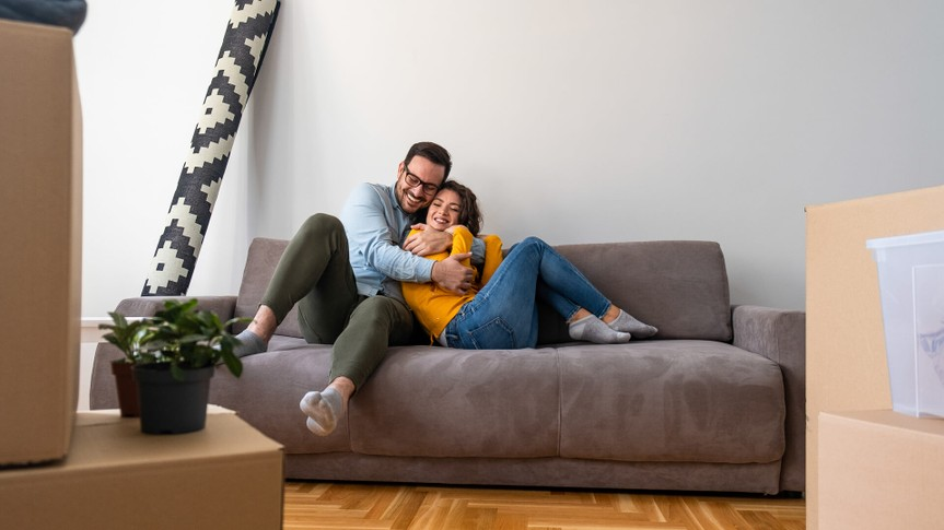 Husband and wife surrounded by cardboard boxes excited to move in new own house apartment.