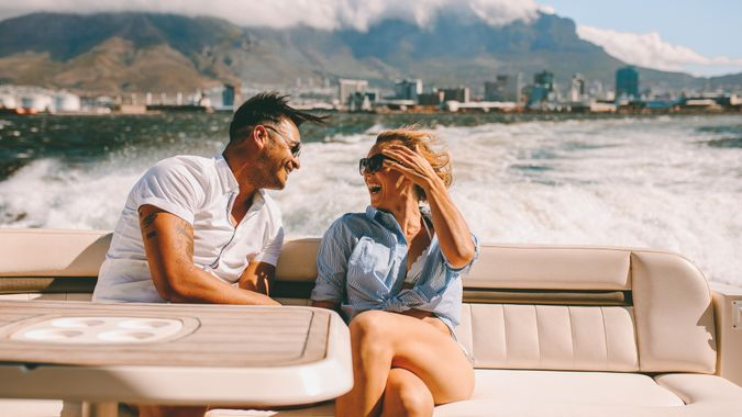 Cheerful young couple sitting on a boat.