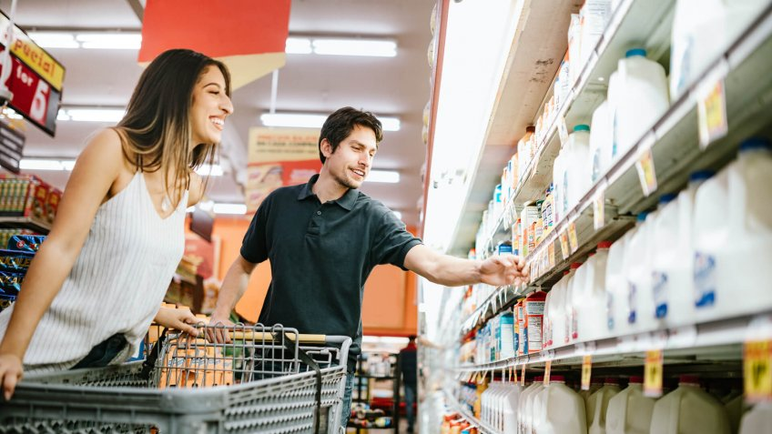 A happy young couple shop for produce and basic foods staples at their local grocery store in Los Angeles, California.