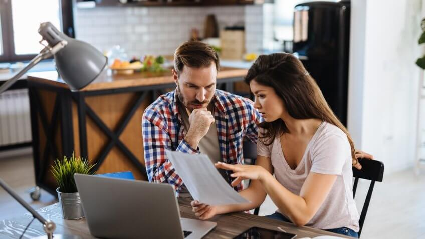 Frustrated couple checking bills at home using laptop.