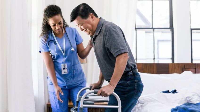 Senior man uses a walker to help him get out off bed.
