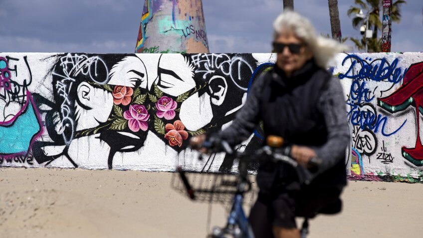 A woman rides her bike past a mural showing a couple kissing with face masks next to the beach amid the coronavirus pandemic in Venice, California, USA, 28 March 2020.
