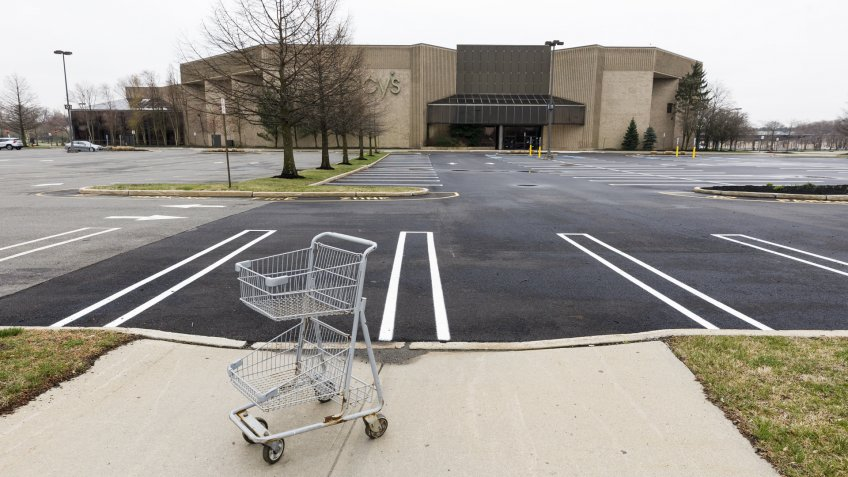 An empty shopping cart in an empty parking lot at a Macy's department store in a mall which is closed to help prevent the spread of the coronavirus, in Paramus, New Jersey, USA, 30 March 2020.