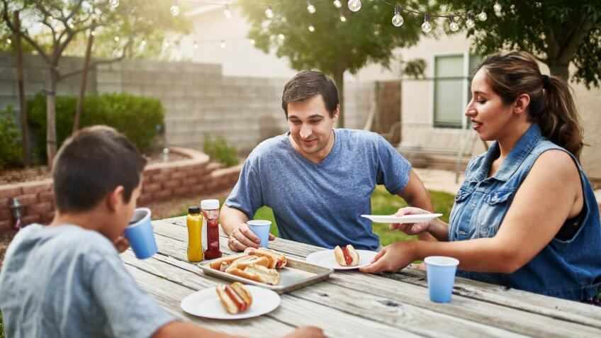 family in backyard picnic table