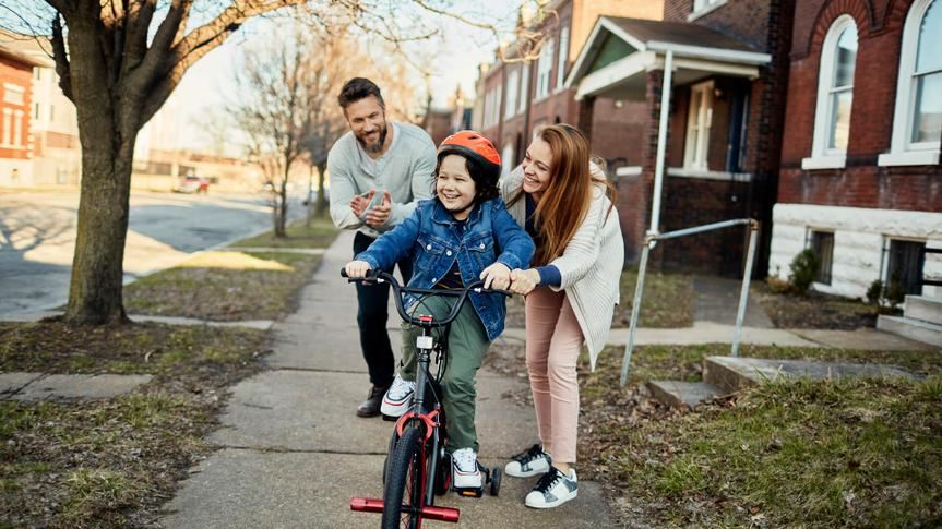 Close up of a father and mother helping their son with learning how to ride a bike.
