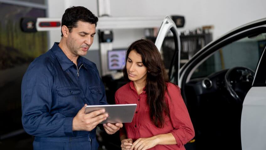 Friendly mechanic showing female customer the work done on her car on tablet at the car workshop both smiling.