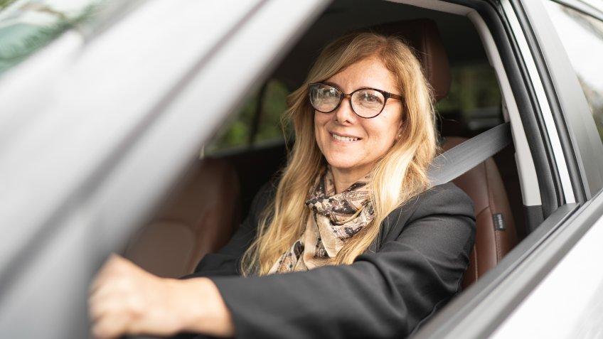 Portrait of a female driver smiling inside a car.