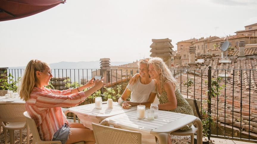 Three female friends sitting down at a table in a rooftop restaurant.